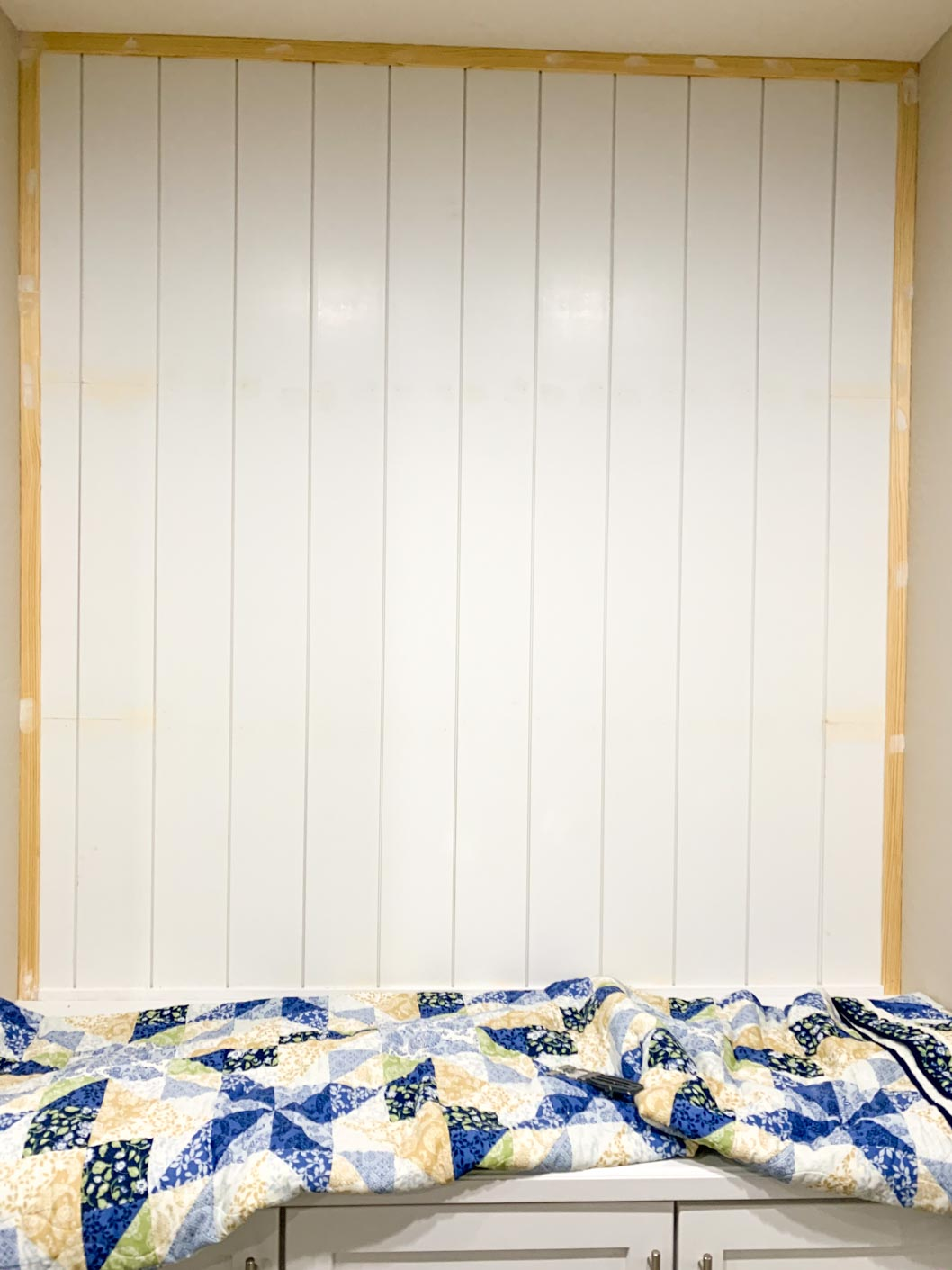white vertical shiplap surrounded by a brown trim on all 4 sides.