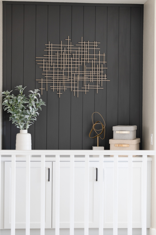 black vertical shiplap on top of white cabinets.
