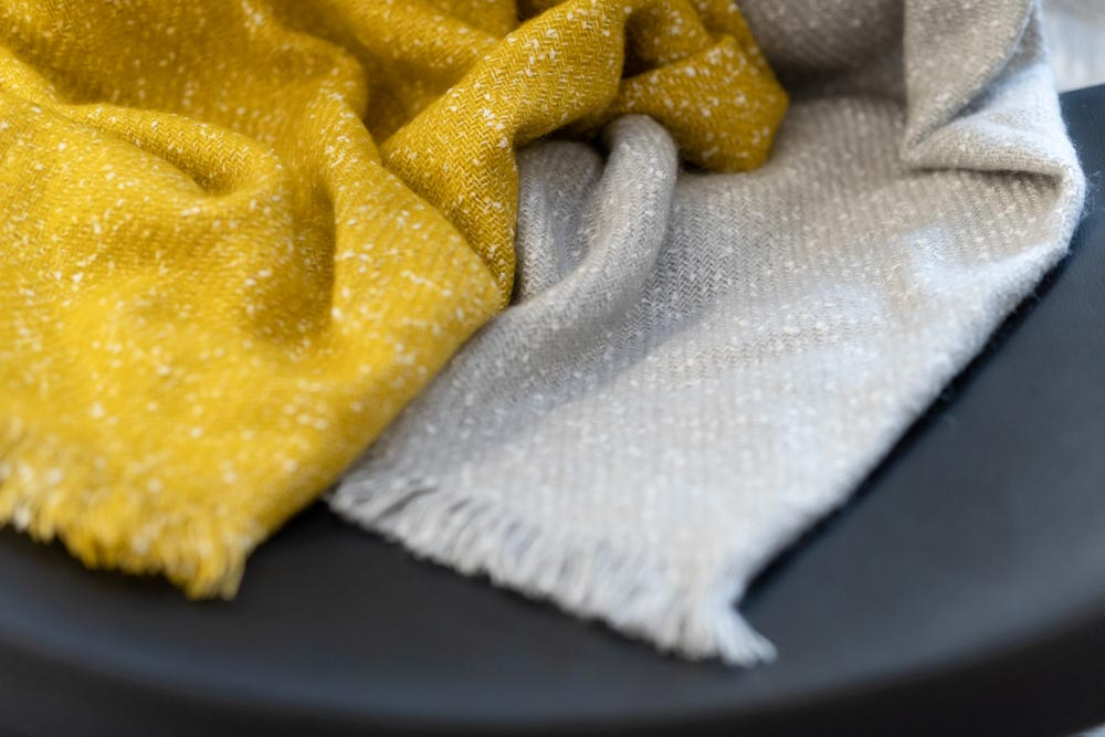 Affordable entryway home decor - speckled gray throw and speckled mustard throw.
