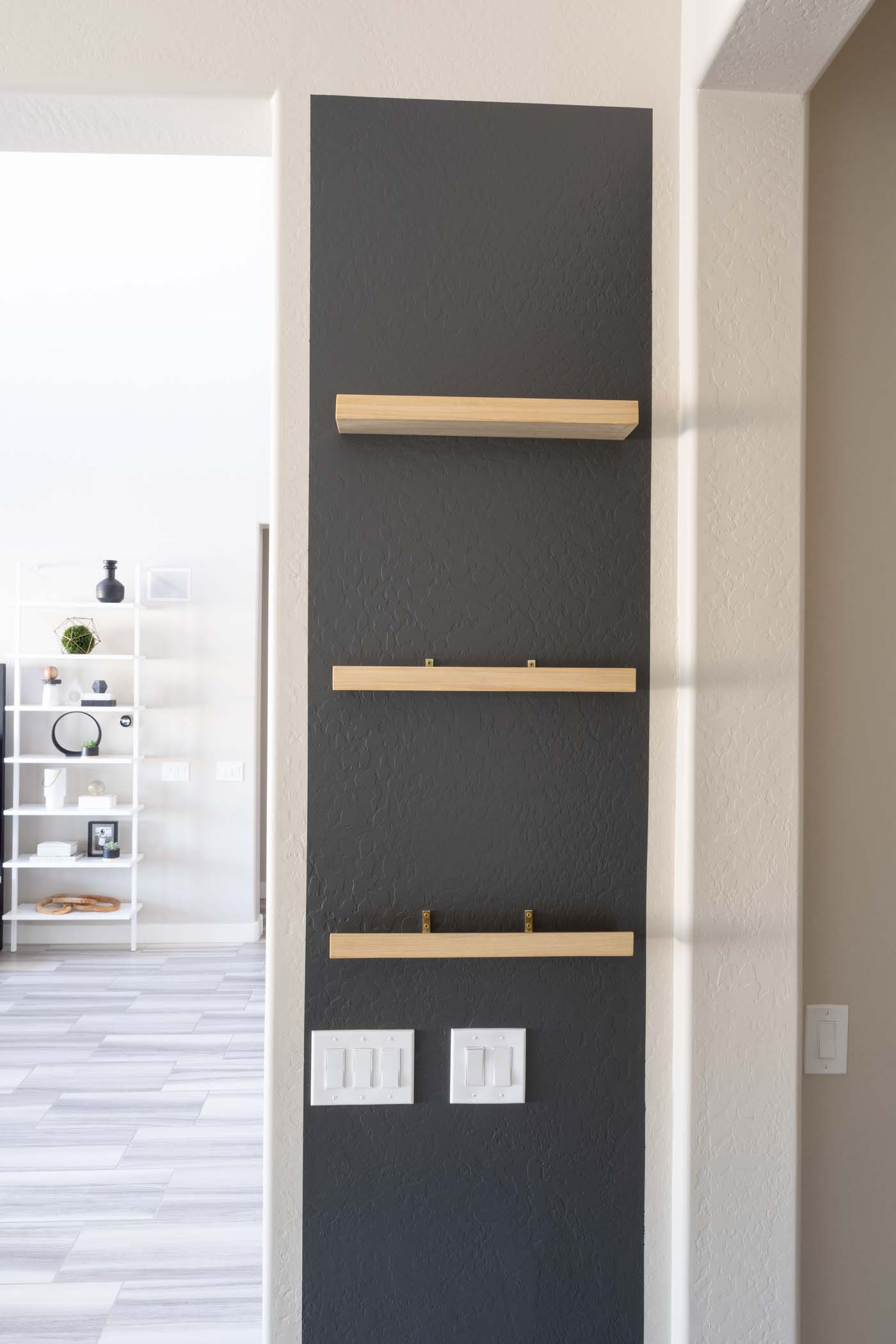 black wall with wooden shelves