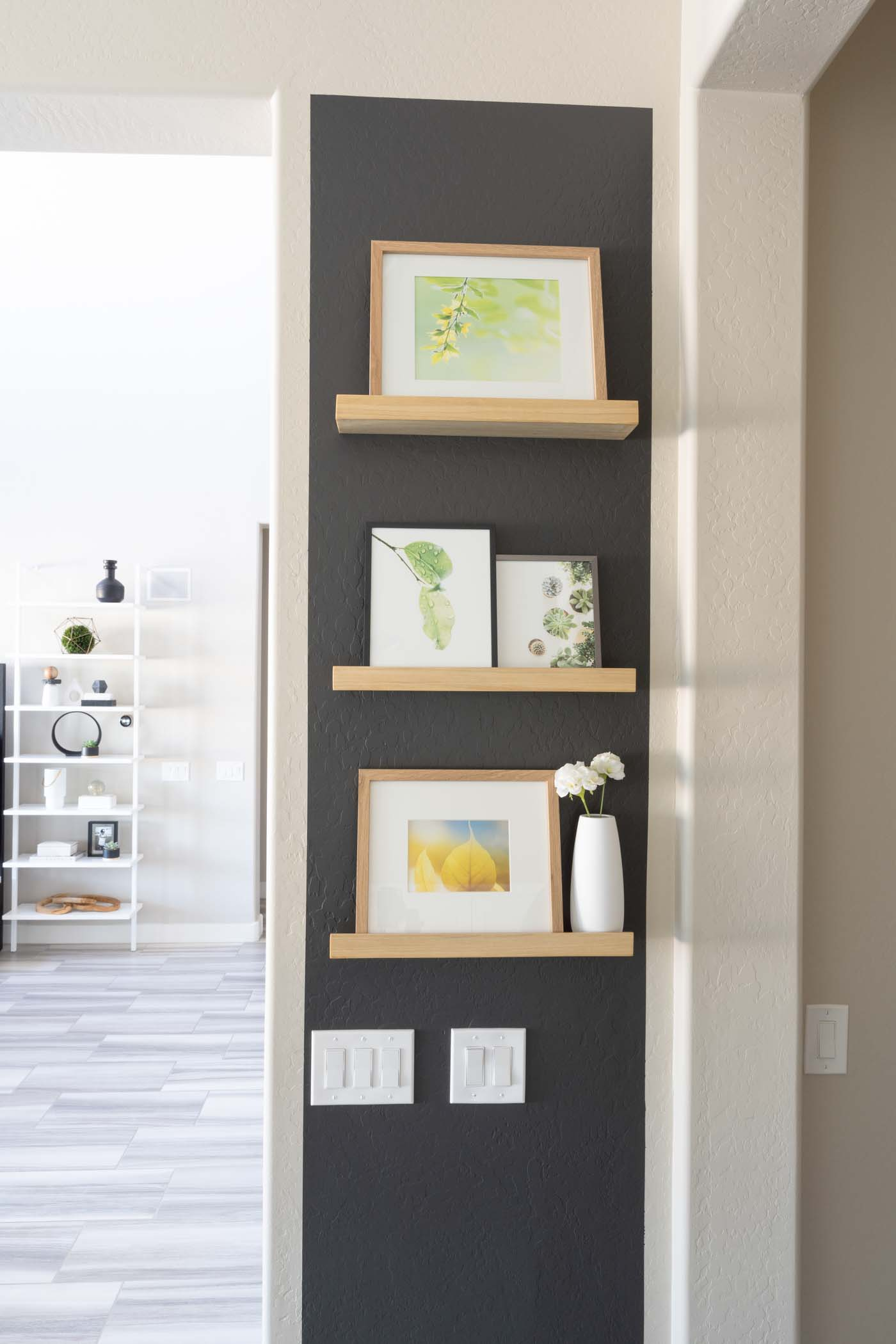 black wall with wooden shelves and picture frames
