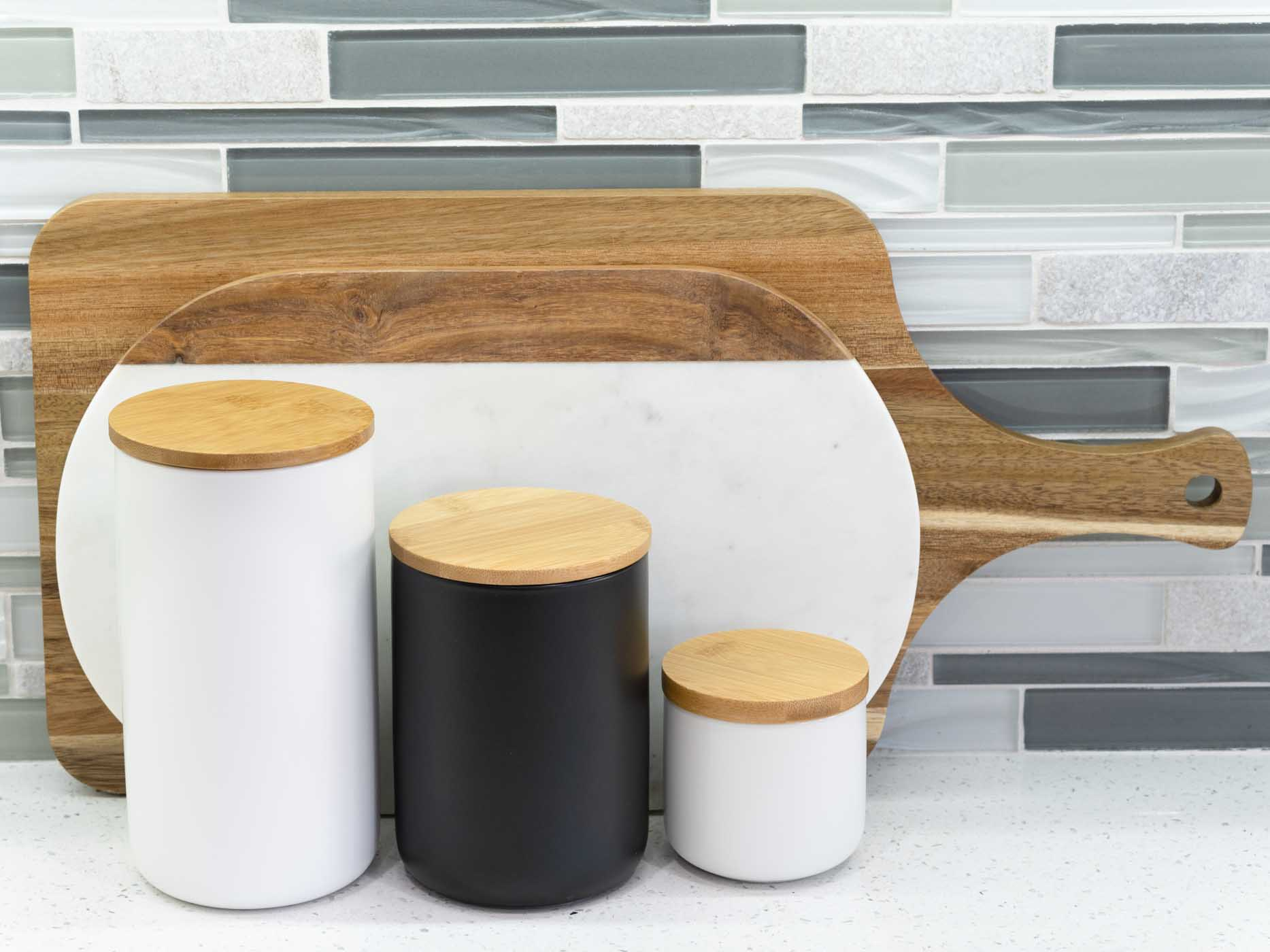 wooden cutting boards with black and white storage canisters on a white kitchen countertop