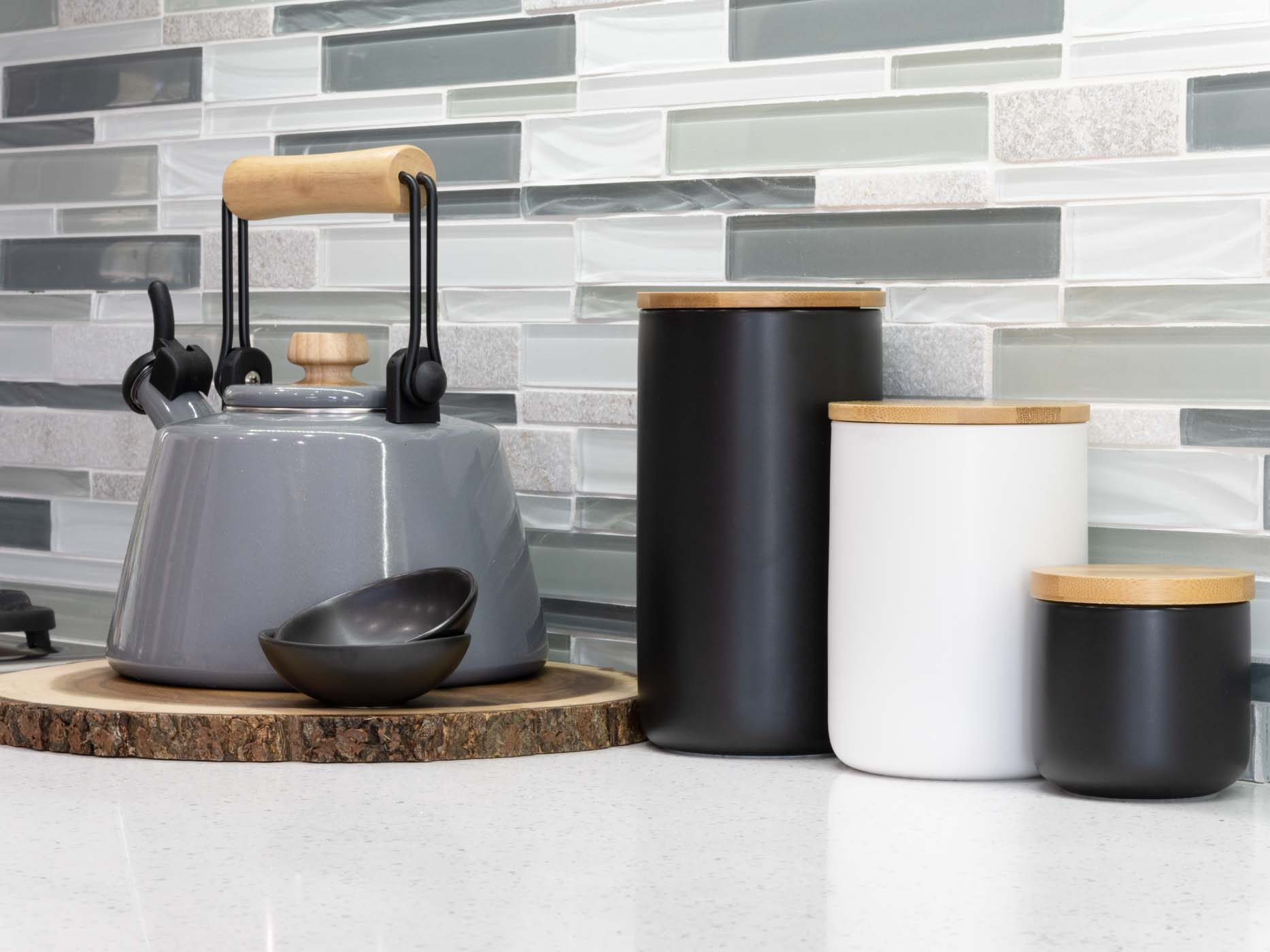 gray kettle with black and white storage canisters on a kitchen countertop