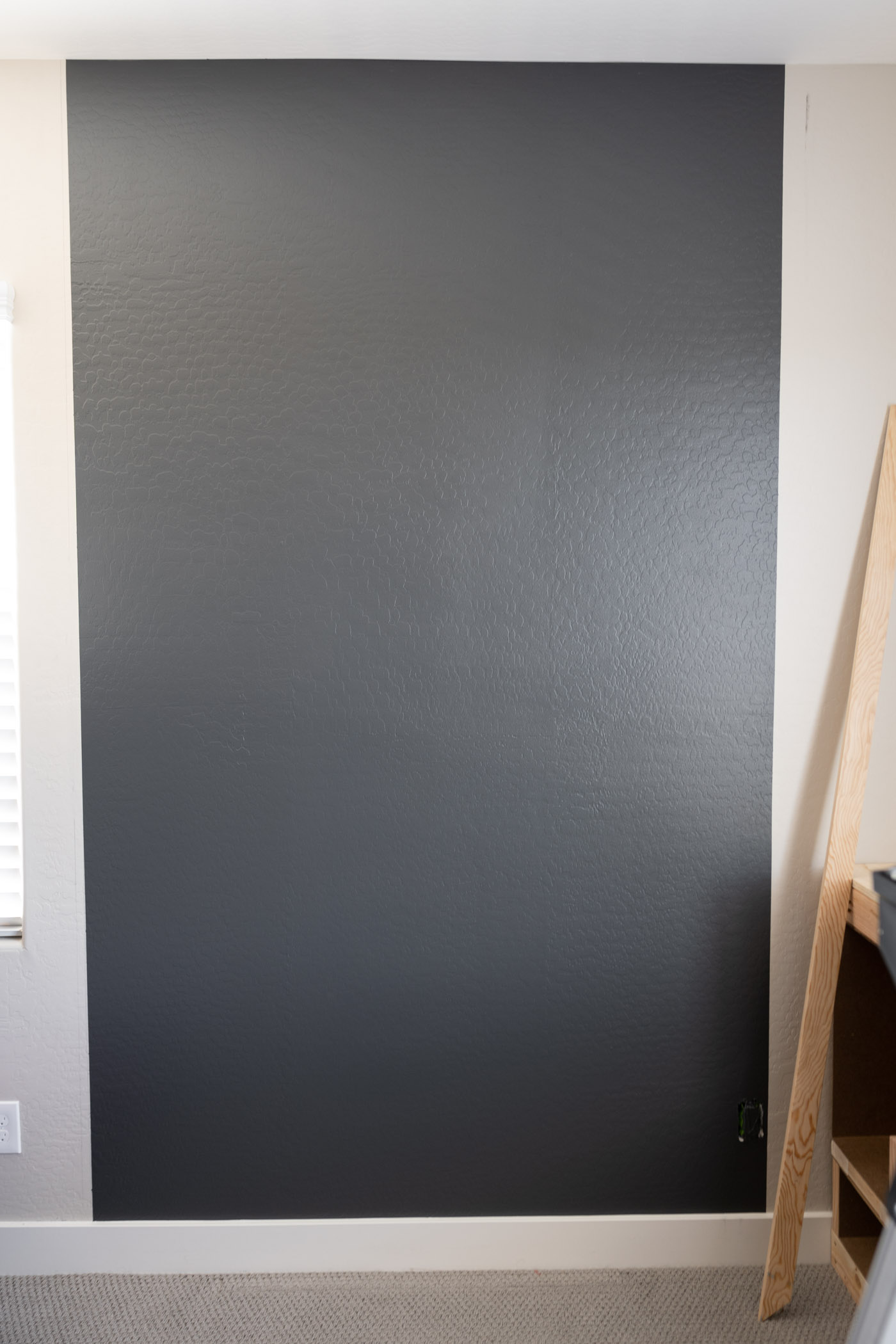 Painted the area for the DIY slat wall in a dark gray paint color.