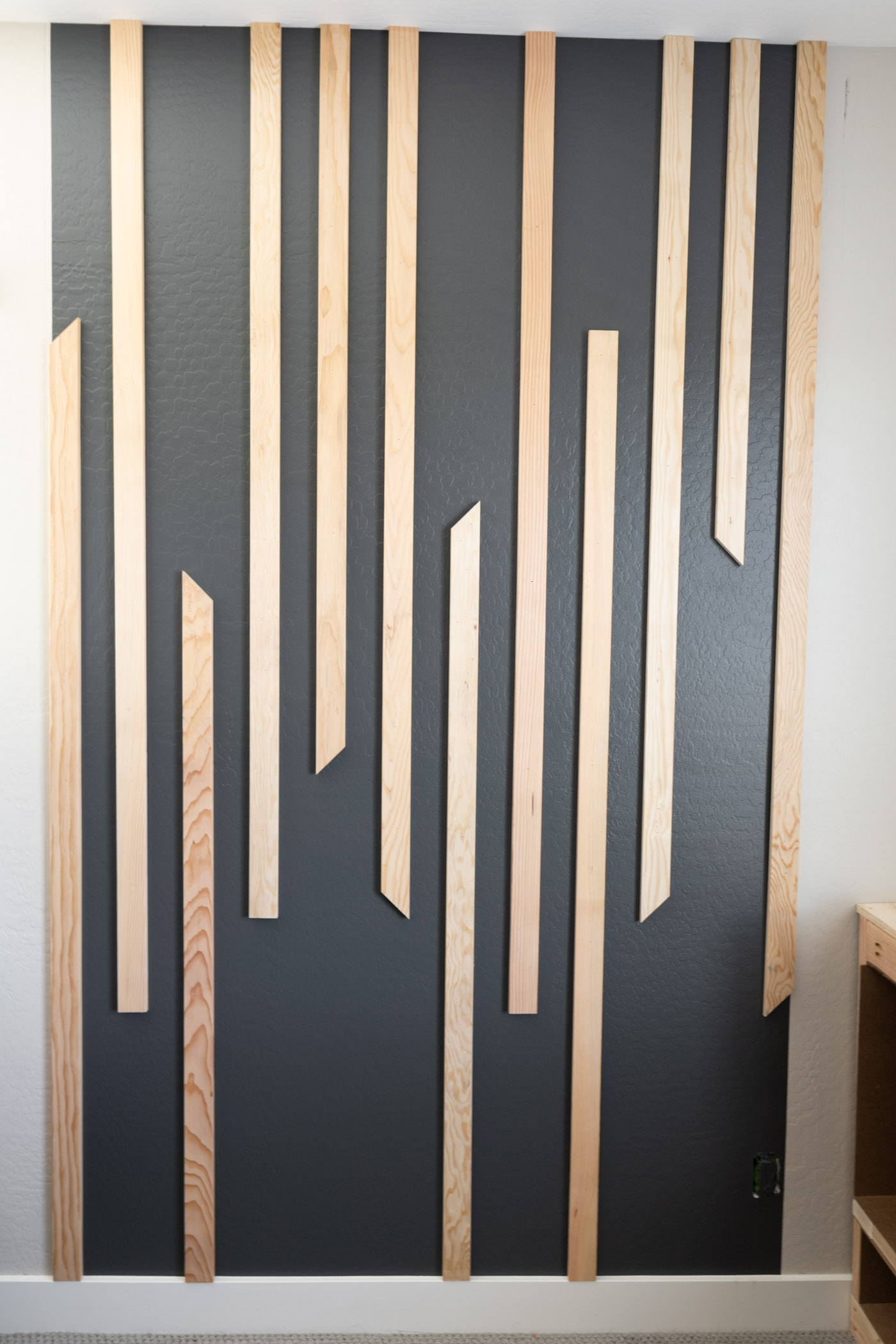 12 Wood board are installed 3 inches apart to create the DIY slat wall.
