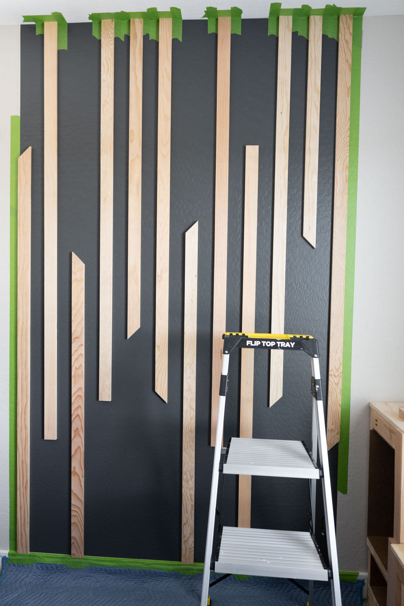 Paint wood boards to complete the DIY slat wall look.