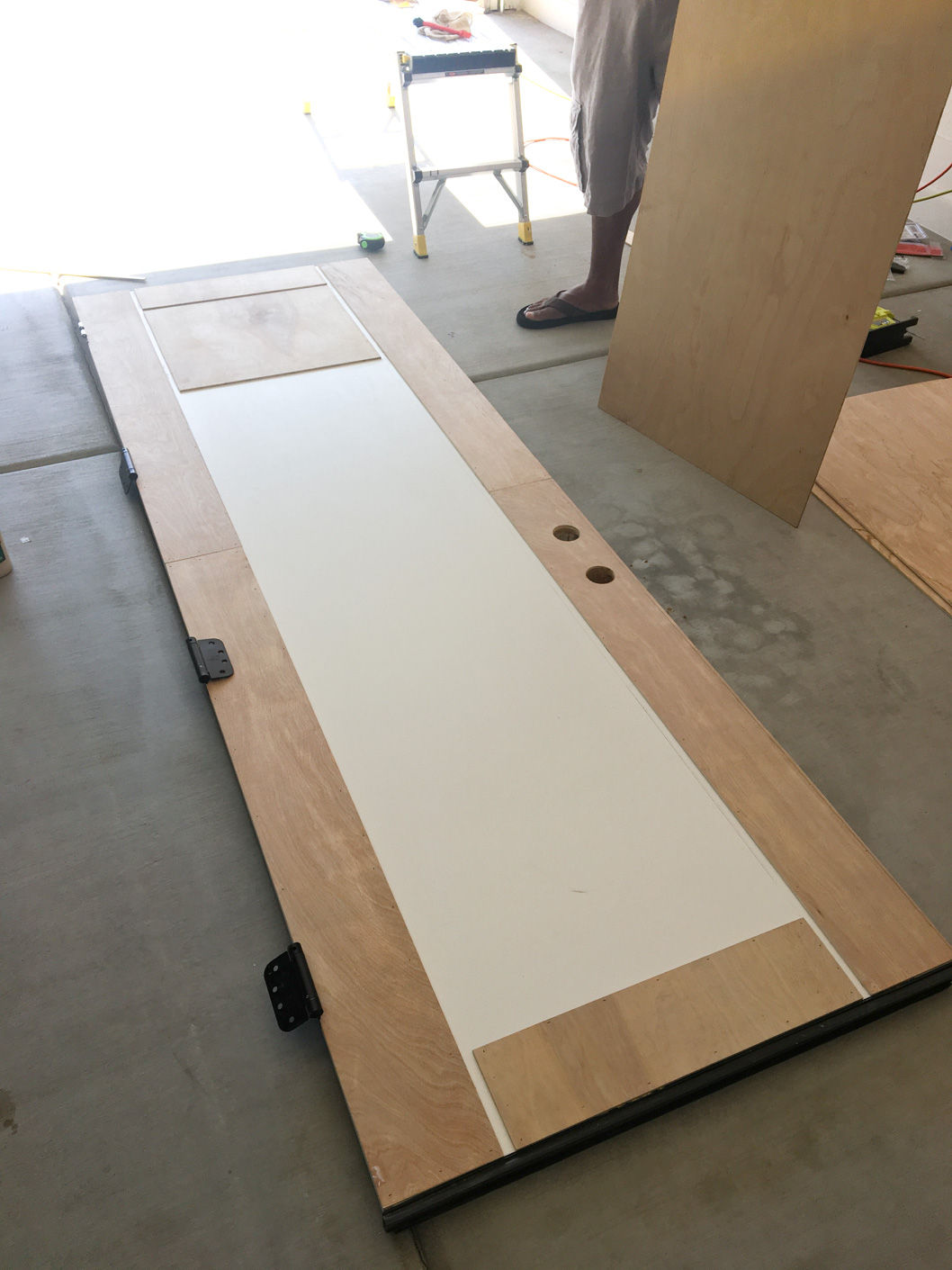 Old, white garage door with 2 vertical wood panels and 3 horizontal wood panels.