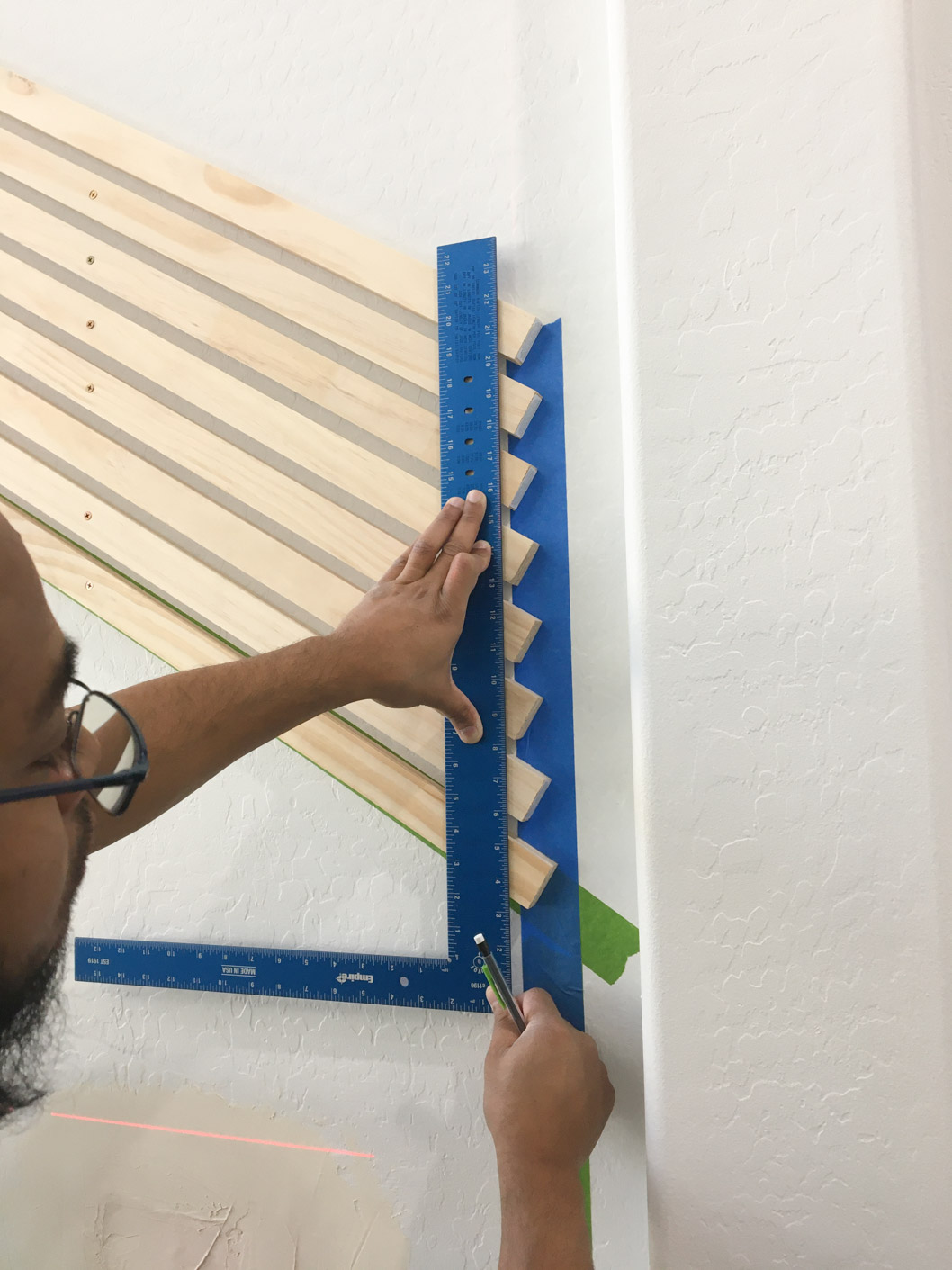Using a ruler to draw a vertical line down the diagonal wood slat pieces.