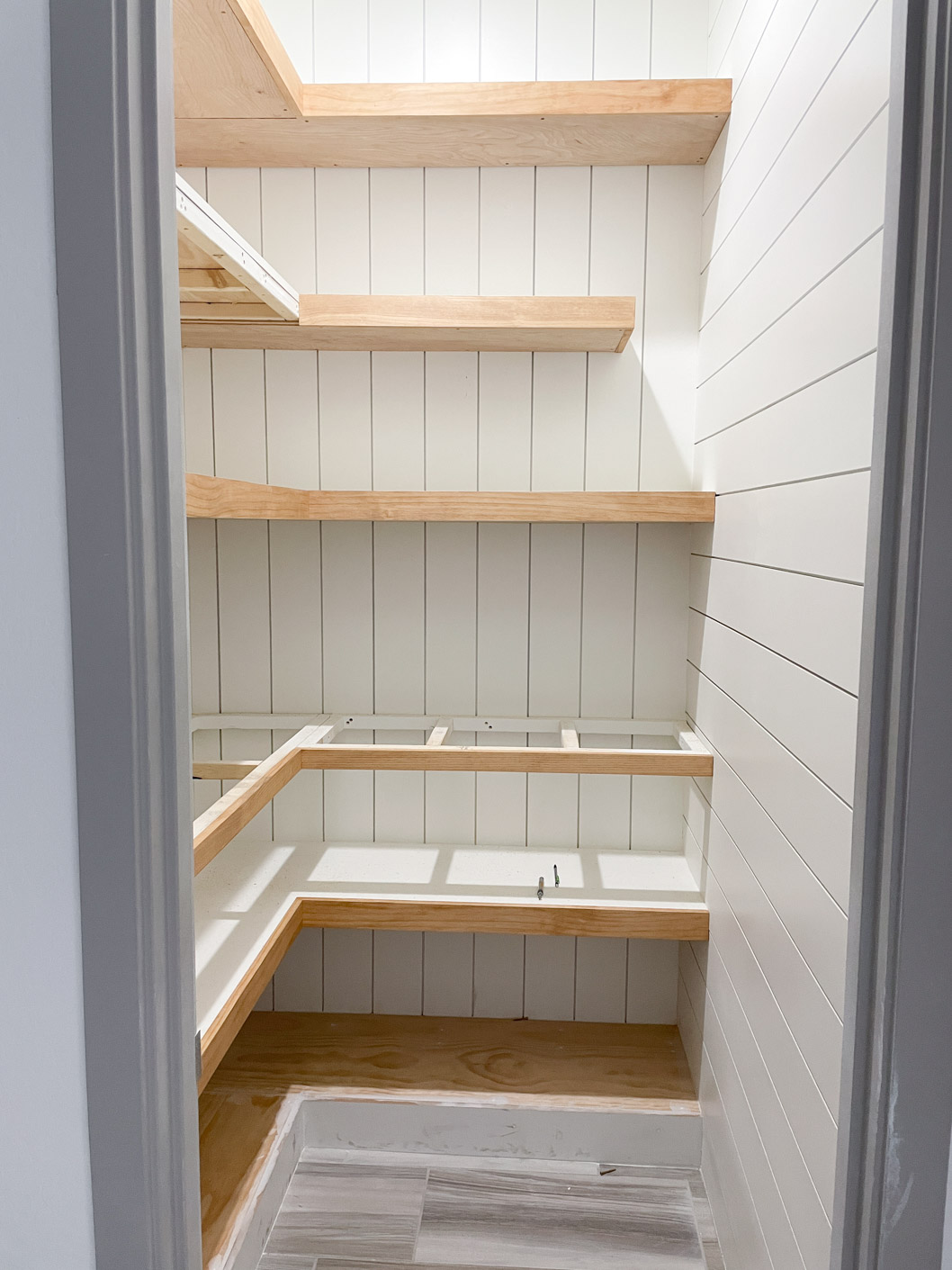 a picture showing white shiplap walls and brown shelves