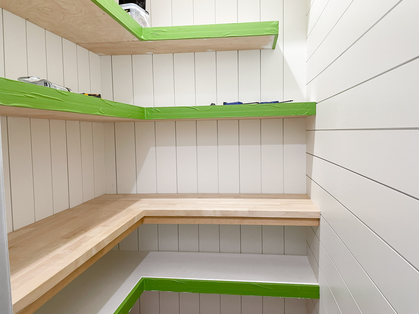 a picture showing white shiplap walls, wooden shelves and a wooden countertop