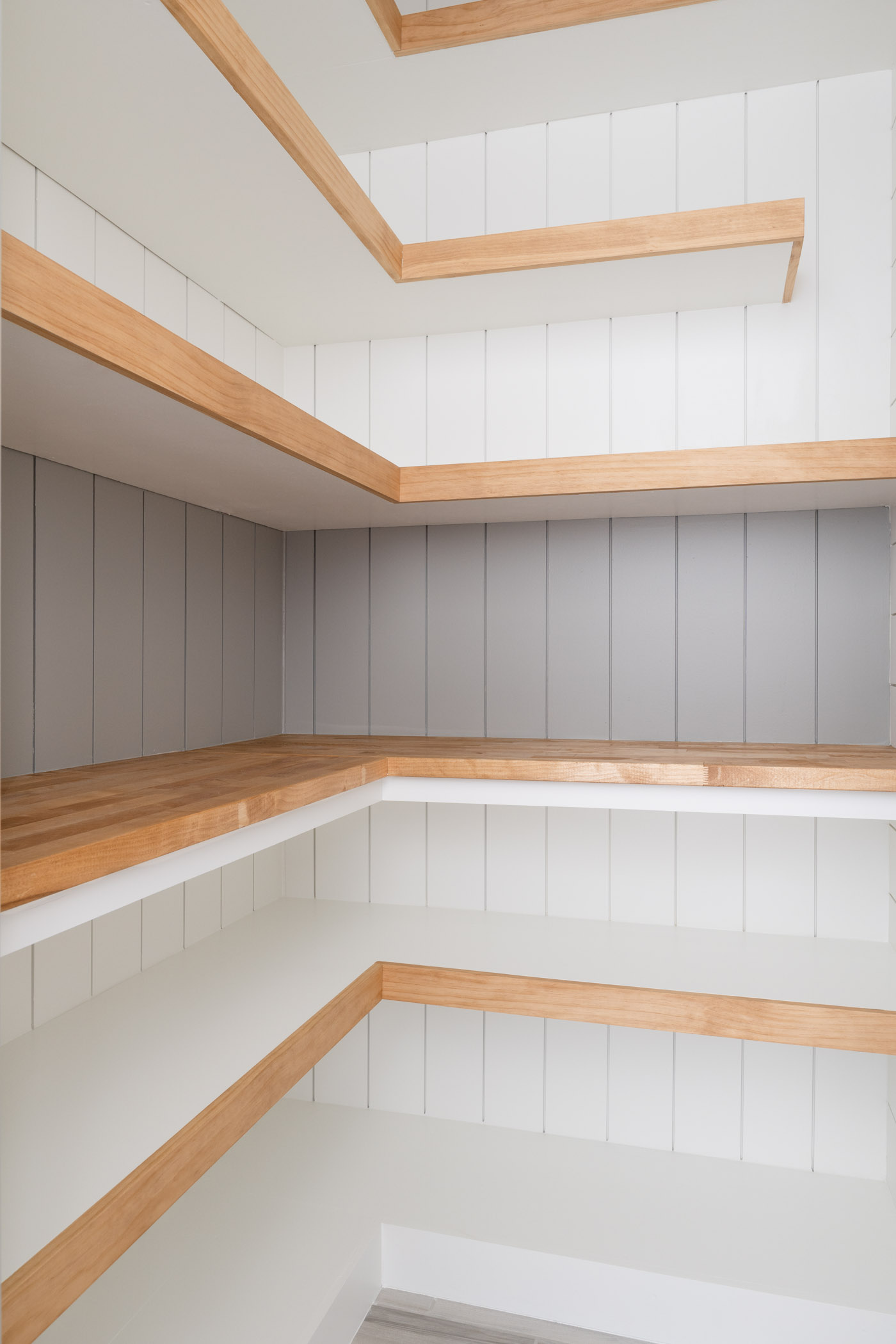white shiplap walls with white and brown open shelving