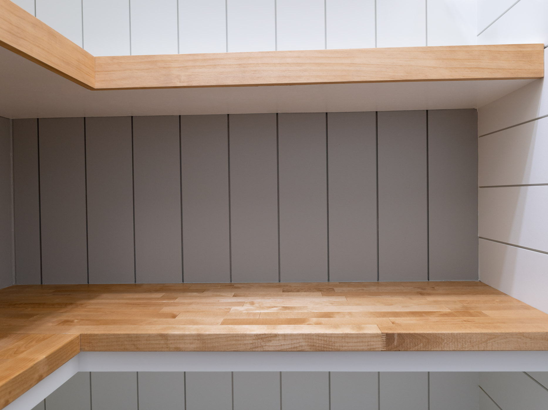 a picture showing white and gray shiplap walls, brown and white shelves and a wooden countertop