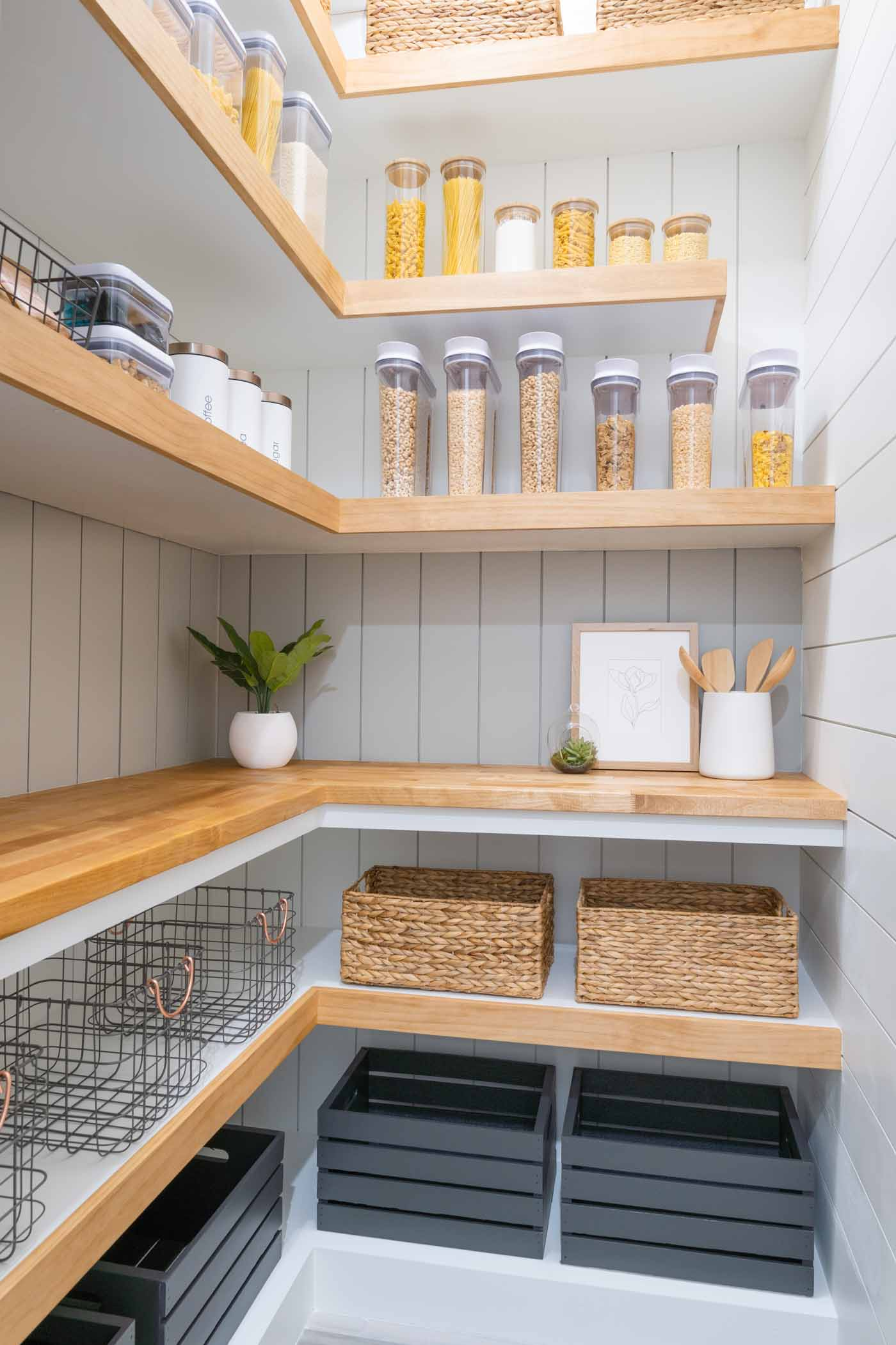 a picture of a pantry with white and gray shiplap walls, brown and white shelves, a wooden countertop, brown baskets, glass storage jars with bamboo lids, white canisters, wooden crates and metal baskets