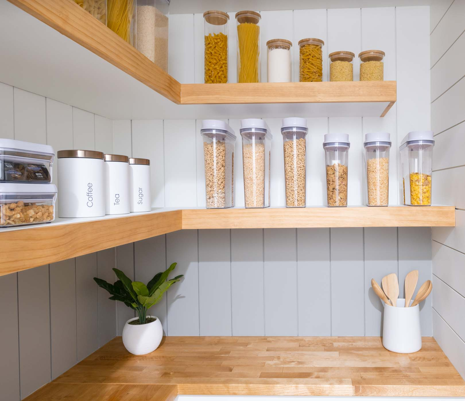 a picture of a pantry with white and gray shiplap walls, shelves, a countertop and storage containers
