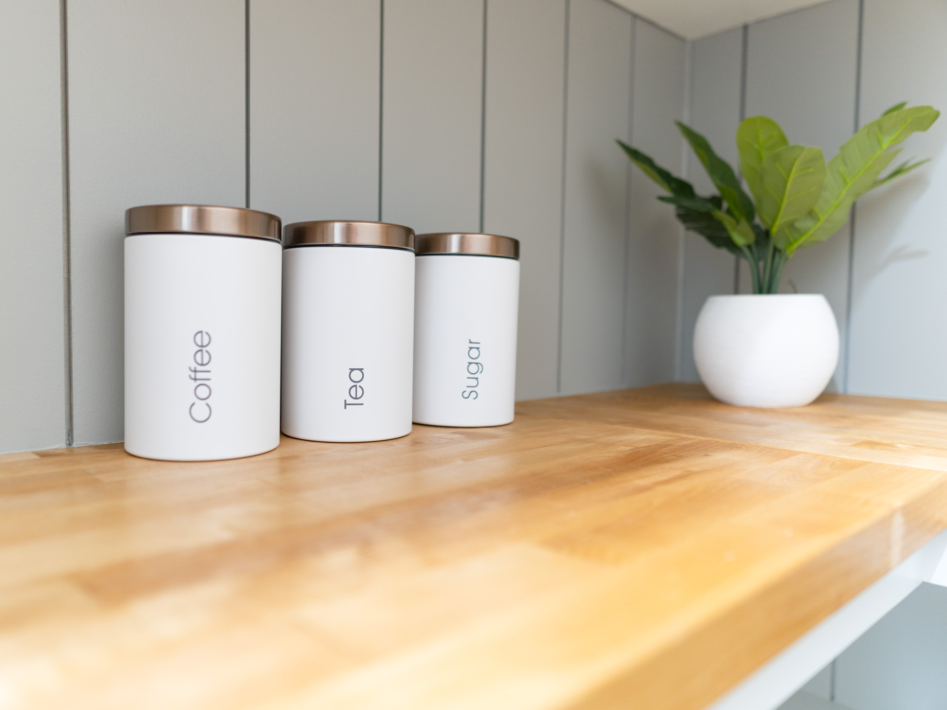 a picture showing 3 white storage canisters on a wooden countertop