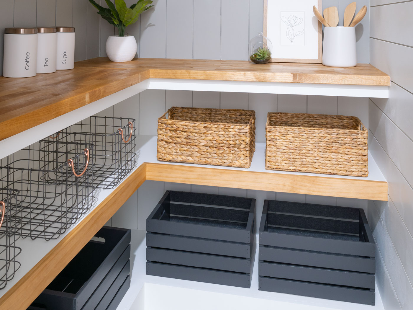 woven baskets, wire metal baskets and black wooden crates on white and brown shelves