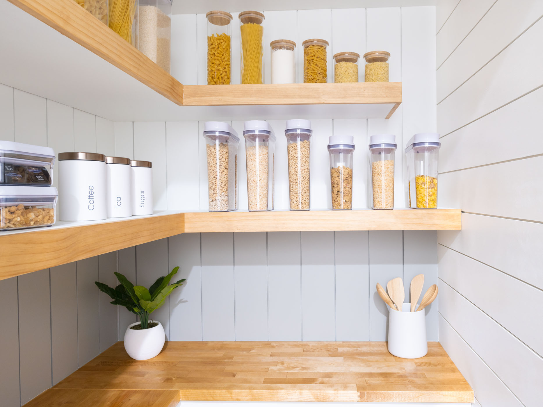 glass jars, plastic jars and metal canisters on white and brown shelves
