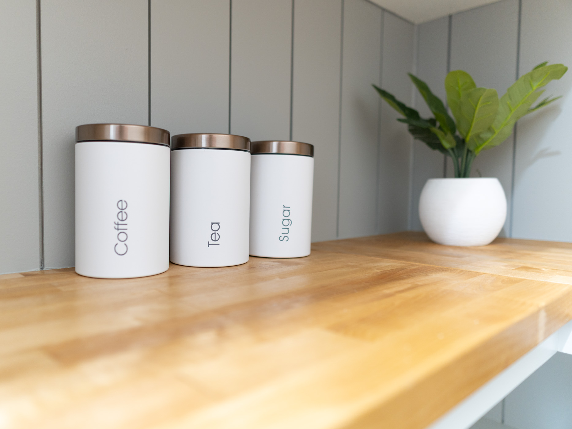 white metal canisters on brown butcher block countertop