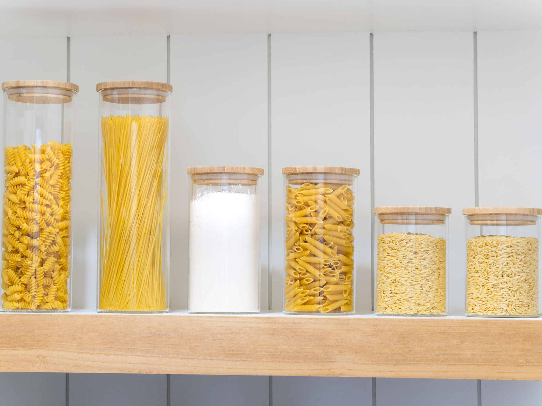 glass jars with wood lids on a white and brown shelf