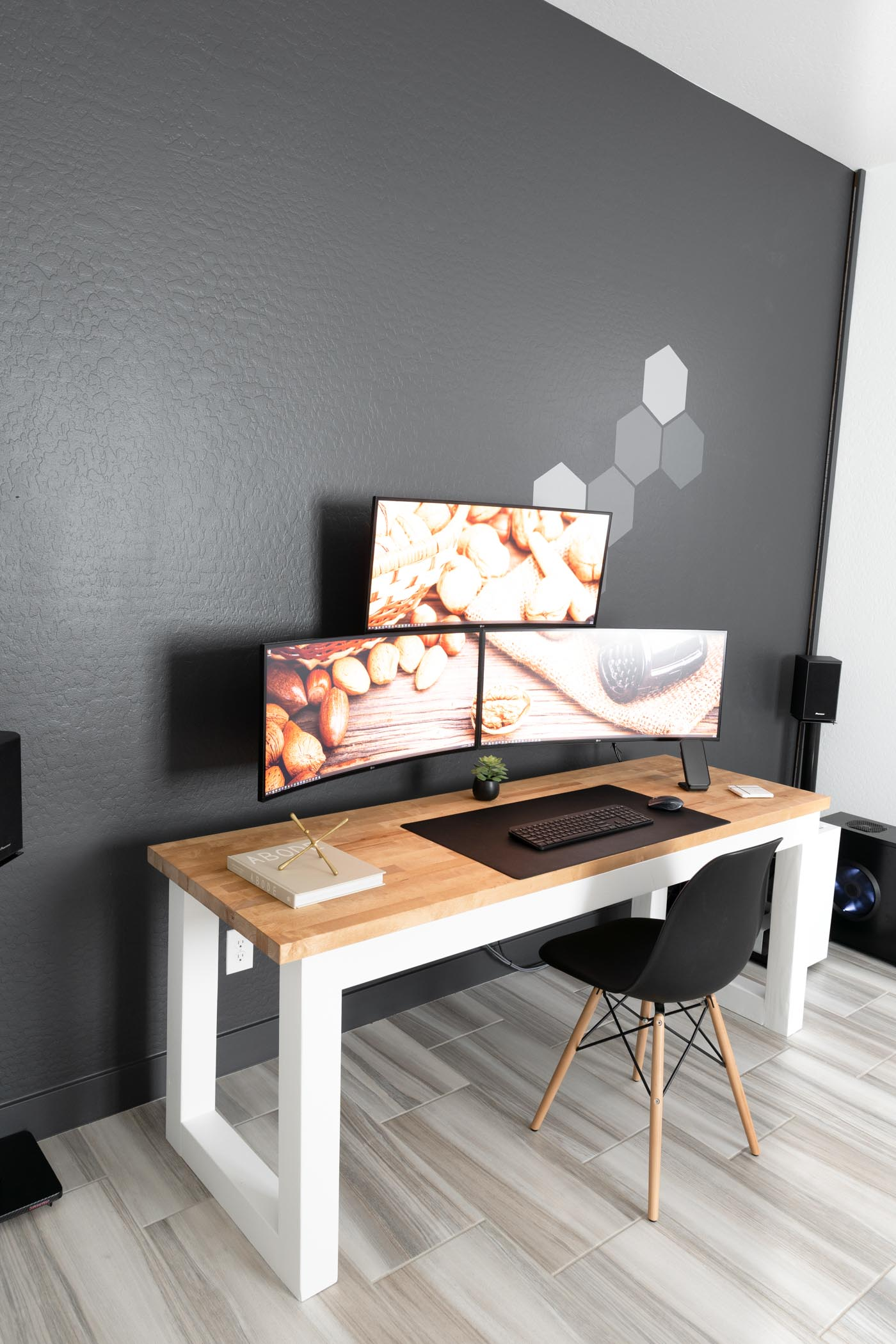 wooden desk with black chair and computer monitors