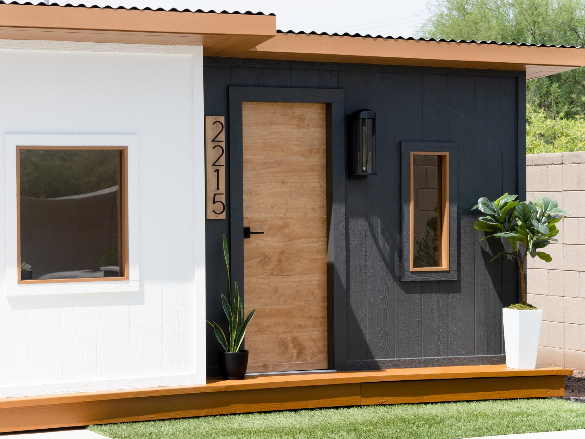 Black and white house with DIY paneled wooden exterior door